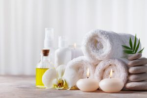 Spa, beauty treatment and wellness background with massage pebbles, orchid flowers, towels, cosmetic products and burning candles. Copy space for text.